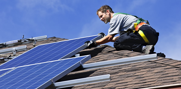 Contractor working on installing solar panels on a residential house's roof